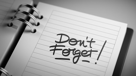 not lined: Closeup of a personal agenda setting an important date representing a time schedule. The words Don`t Forget written on a white notebook to remind you an important appointment. Stock Photo