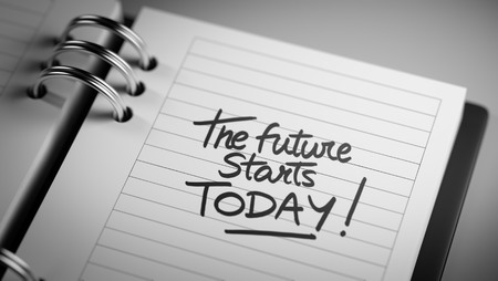 black empowerment: Closeup of a personal agenda setting an important date representing a time schedule. The words The future starts today written on a white notebook to remind you an important appointment. Stock Photo