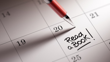 appointment book: Closeup of a personal agenda setting an important date written with pen. The words Read a book written on a white notebook to remind you an important appointment.
