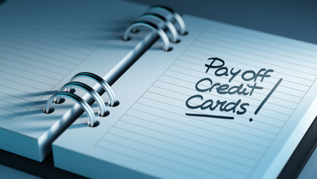 pay off: Closeup of a personal agenda setting an important date representing a time schedule. The words Pay off Credit cards written on a white notebook to remind you an important appointment. Stock Photo