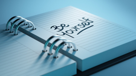 be yourself: Closeup of a personal agenda setting an important date representing a time schedule. The words be yourself written on a white notebook to remind you an important appointment. Stock Photo