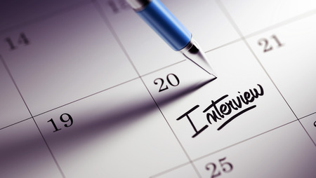 oral communication: Closeup of a personal agenda setting an important date written with pen. The words Interview written on a white notebook to remind you an important appointment.