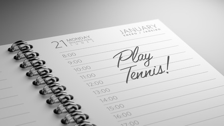 play date: Closeup of a personal calendar setting an important date representing a time schedule. The words Play Tennis written on a white notebook to remind you an important appointment.