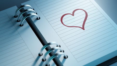 important date: Closeup of a personal agenda setting an important date representing a time schedule. The words heart shape written on a white notebook to remind you an important appointment. Stock Photo