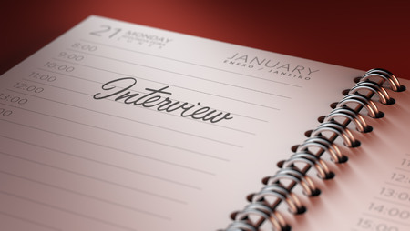 comunicacion oral: Closeup of a personal calendar setting an important date representing a time schedule. The words Interview written on a white notebook to remind you an important appointment.