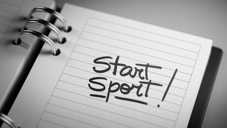 important date: Closeup of a personal agenda setting an important date representing a time schedule. The words Start Sport written on a white notebook to remind you an important appointment. Stock Photo