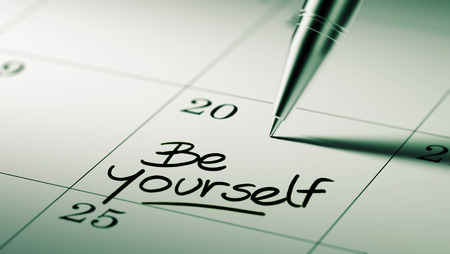 important date: Closeup of a personal agenda setting an important date written with pen. The words be yourself written on a white notebook to remind you an important appointment.