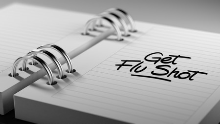 Closeup of a personal agenda setting an important date representing a time schedule. The words Get Flu Shot written on a white notebook to remind you an important appointment. Stock Photo