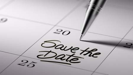 calendar date: Closeup of a personal agenda setting an important date written with pen. The words Save the date written on a white notebook to remind you an important appointment. Stock Photo