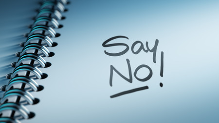 denying: Closeup of a personal calendar setting an important date representing a time schedule. The words Say NO written on a white notebook to remind you an important appointment. Stock Photo