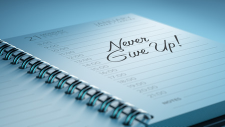 up to date: Closeup of a personal calendar setting an important date representing a time schedule. The words Never give up written on a white notebook to remind you an important appointment.