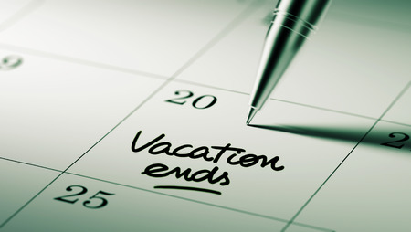 the ends: Closeup of a personal agenda setting an important date written with pen. The words Vacation ends written on a white notebook to remind you an important appointment.