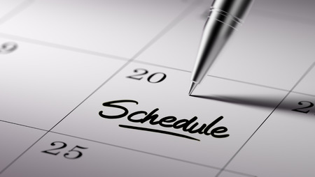 Closeup of a personal agenda setting an important date written with pen. The words Schedule written on a white notebook to remind you an important appointment.