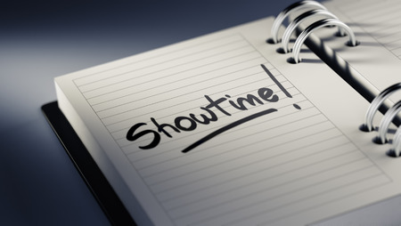 showtime: Closeup of a personal agenda setting an important date representing a time schedule. The words Showtime written on a white notebook to remind you an important appointment.