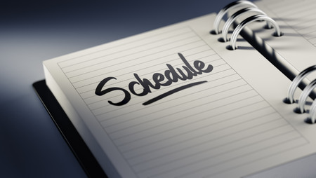 Closeup of a personal agenda setting an important date representing a time schedule. The words Schedule written on a white notebook to remind you an important appointment. Imagens