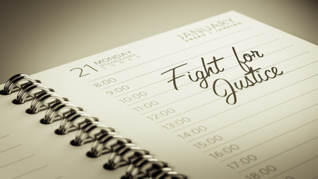 Closeup of a personal calendar setting an important date representing a time schedule. The words Fight for Justice written on a white notebook to remind you an important appointment.