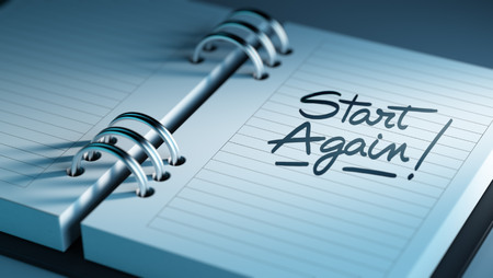 Closeup of a personal agenda setting an important date representing a time schedule. The words Start Again written on a white notebook to remind you an important appointment.