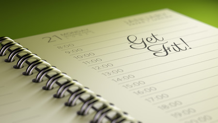 Closeup of a personal calendar setting an important date representing a time schedule. The words Get Fit! written on a white notebook to remind you an important appointment. Imagens
