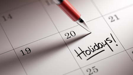 Closeup of a personal agenda setting an important date written with pen. The words Holidays written on a white notebook to remind you an important appointment.