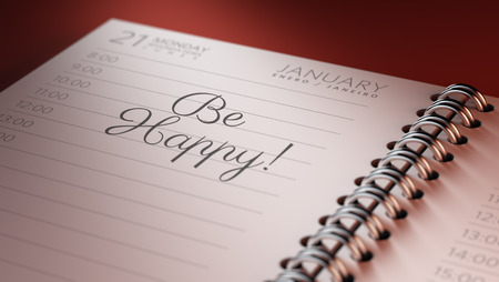 Closeup of a personal calendar setting an important date representing a time schedule. The words Be happy written on a white notebook to remind you an important appointment.