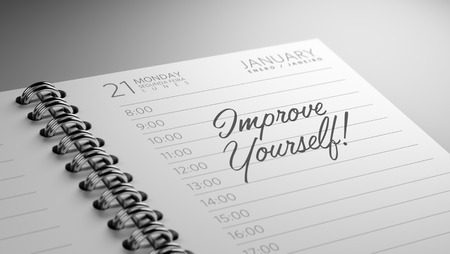 Closeup of a personal calendar setting an important date representing a time schedule. The words Improve yourself written on a white notebook to remind you an important appointment.