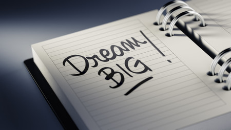 Closeup of a personal agenda setting an important date representing a time schedule. The words Dream big written on a white notebook to remind you an important appointment. Imagens