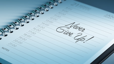 Closeup of a personal calendar setting an important date representing a time schedule. The words Never give up written on a white notebook to remind you an important appointment.