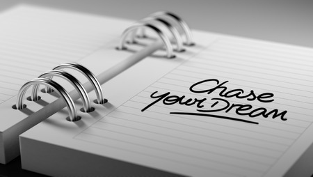 Closeup of a personal agenda setting an important date representing a time schedule. The words Chase your dream written on a white notebook to remind you an important appointment. Imagens