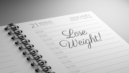 Closeup of a personal calendar setting an important date representing a time schedule. The words Lose Weight written on a white notebook to remind you an important appointment.