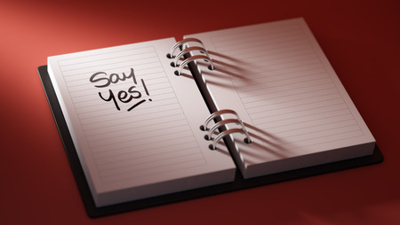 Closeup of a personal agenda setting an important date representing a time schedule. The words Say Yes written on a white notebook to remind you an important appointment.