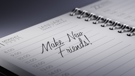 Closeup of a personal calendar setting an important date representing a time schedule. The words Make new friends written on a white notebook to remind you an important appointment.