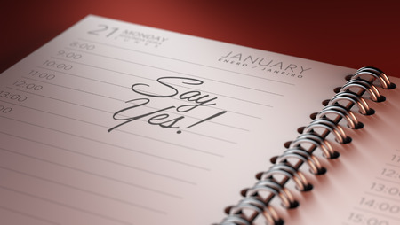 Closeup of a personal calendar setting an important date representing a time schedule. The words Say Yes written on a white notebook to remind you an important appointment.