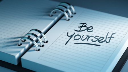 Closeup of a personal agenda setting an important date representing a time schedule. The words be yourself written on a white notebook to remind you an important appointment. Imagens