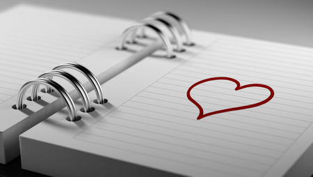 Closeup of a personal agenda setting an important date representing a time schedule. The words heart shape written on a white notebook to remind you an important appointment. Imagens