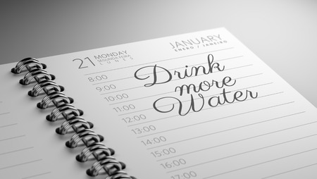 Closeup of a personal calendar setting an important date representing a time schedule. The words Drink more water written on a white notebook to remind you an important appointment. Imagens