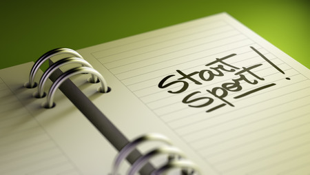 Closeup of a personal agenda setting an important date representing a time schedule. The words Start Sport written on a white notebook to remind you an important appointment. Imagens