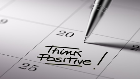 Closeup of a personal agenda setting an important date written with pen. The words Think positive written on a white notebook to remind you an important appointment.