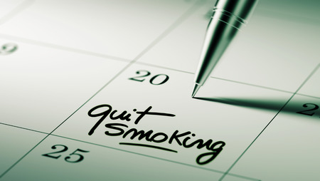 Closeup of a personal agenda setting an important date written with pen. The words Quit Smoking written on a white notebook to remind you an important appointment.