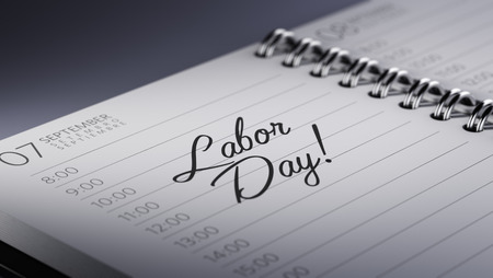 Closeup of a personal calendar setting an important date representing a time schedule. The words Labor Day written on a white notebook to remind you an important appointment.