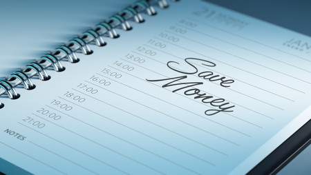 Closeup of a personal calendar setting an important date representing a time schedule. The words Save Money written on a white notebook to remind you an important appointment.