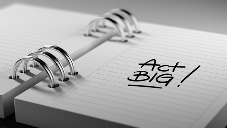 Closeup of a personal agenda setting an important date representing a time schedule. The words Act BIG written on a white notebook to remind you an important appointment. Imagens