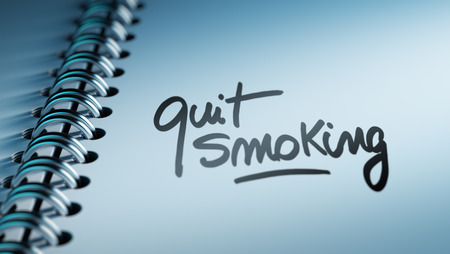 Closeup of a personal calendar setting an important date representing a time schedule. The words Quit Smoking written on a white notebook to remind you an important appointment. Imagens