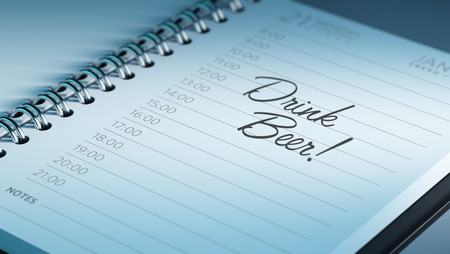 Closeup of a personal calendar setting an important date representing a time schedule. The words Drink a beer written on a white notebook to remind you an important appointment.