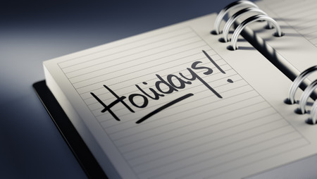 Closeup of a personal agenda setting an important date representing a time schedule. The words Holidays written on a white notebook to remind you an important appointment. Imagens