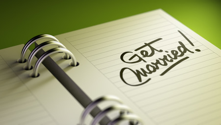 Closeup of a personal agenda setting an important date representing a time schedule. The words Get Married written on a white notebook to remind you an important appointment. Imagens
