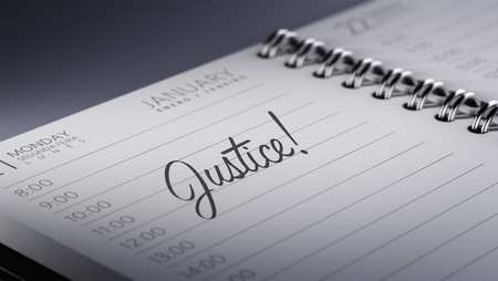 Closeup of a personal calendar setting an important date representing a time schedule. The words Justice written on a white notebook to remind you an important appointment. Imagens