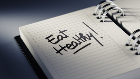 Closeup of a personal agenda setting an important date representing a time schedule. The words Eat Healthy written on a white notebook to remind you an important appointment. Imagens
