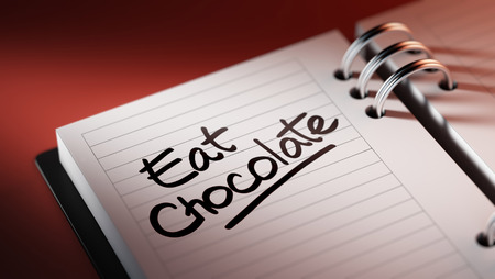 Closeup of a personal agenda setting an important date representing a time schedule. The words Eat Chocolate written on a white notebook to remind you an important appointment.