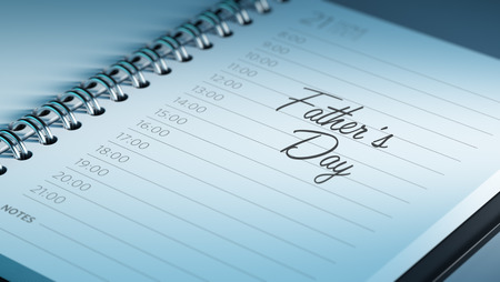 Closeup of a personal calendar setting an important date representing a time schedule. The words Fathers Day written on a white notebook to remind you an important appointment.