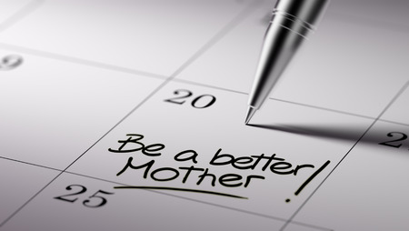 Closeup of a personal agenda setting an important date written with pen. The words Be a better mother written on a white notebook to remind you an important appointment.